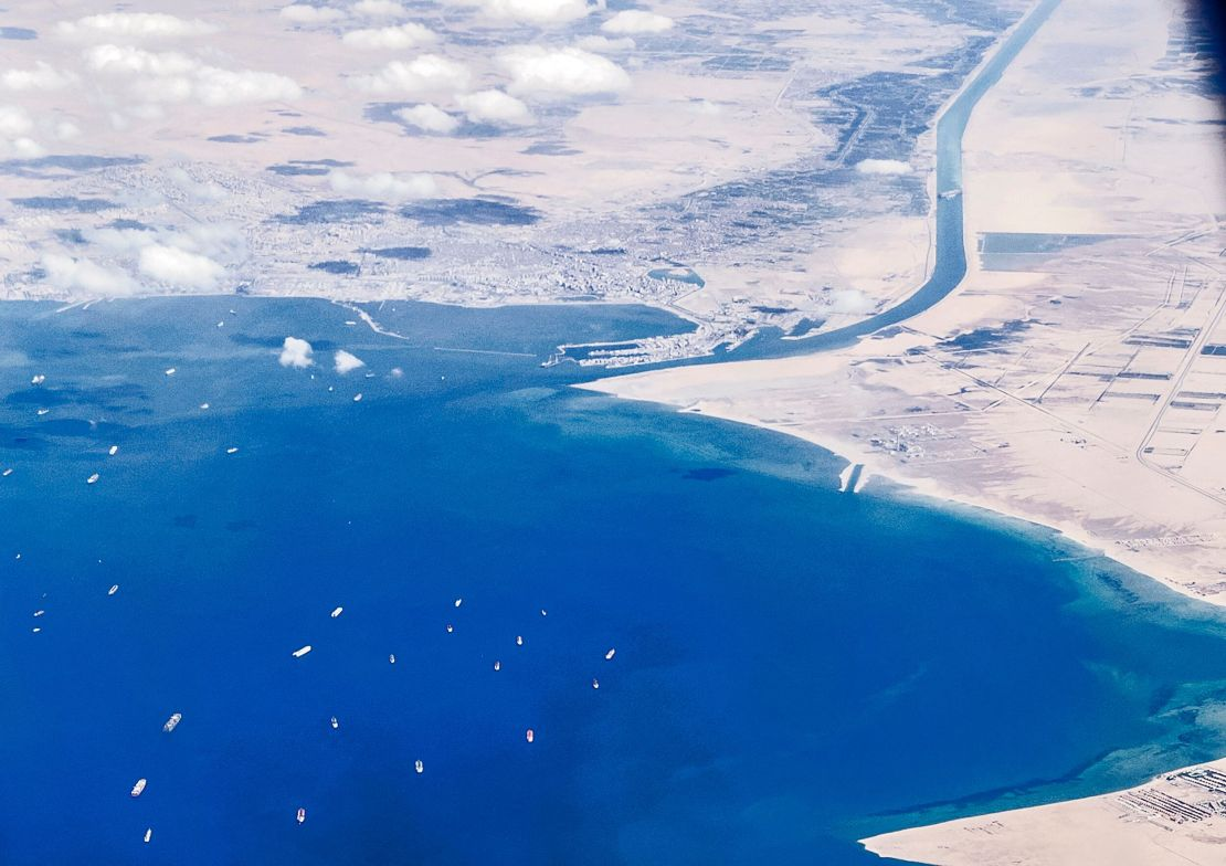 An aerial view taken on March 27, 2021 from the porthole of a commercial plane shows stranded ships waiting in line in the Gu