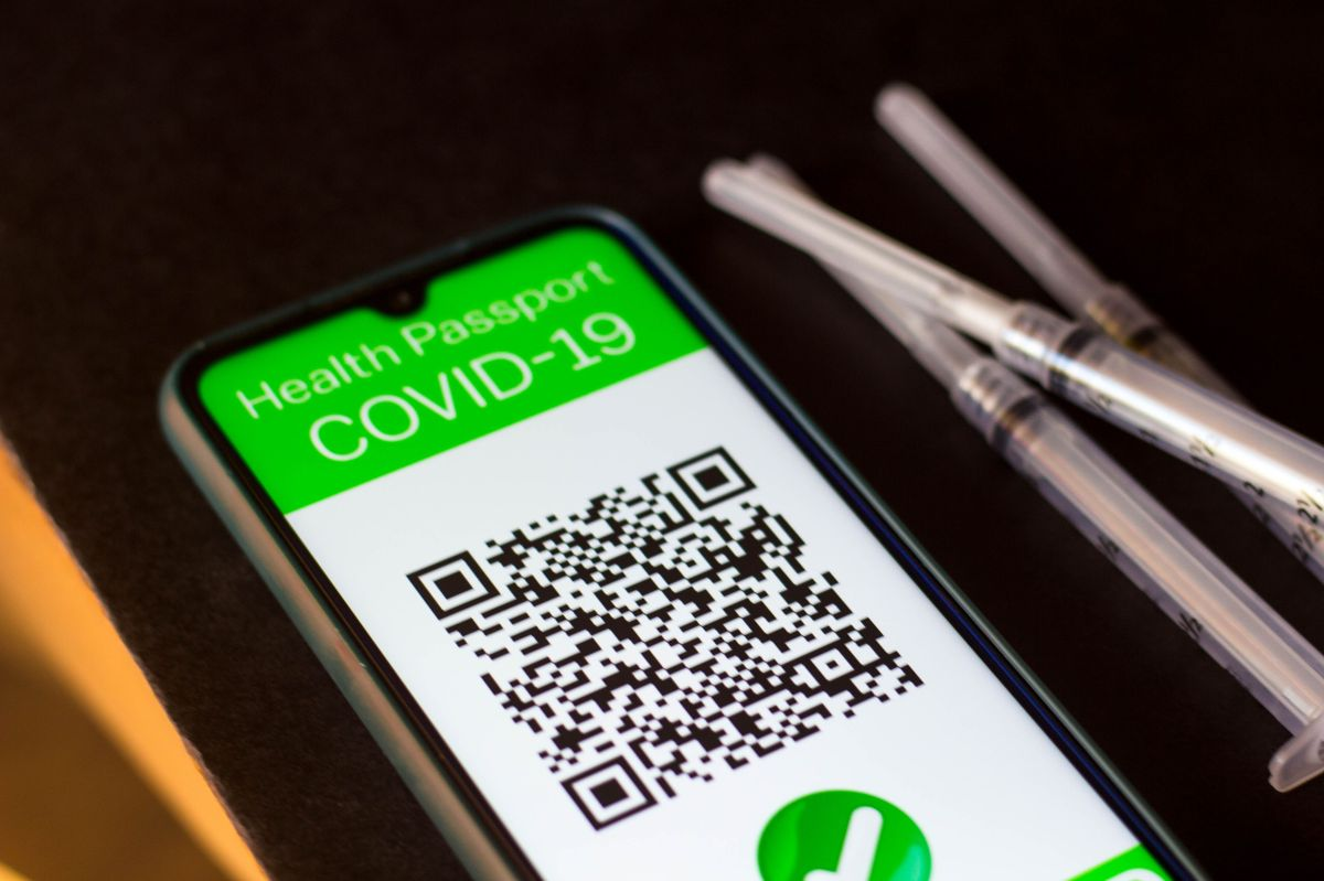 In this photo illustration a symbolic Covid-19 health passport seen on a smartphone screen next to the...