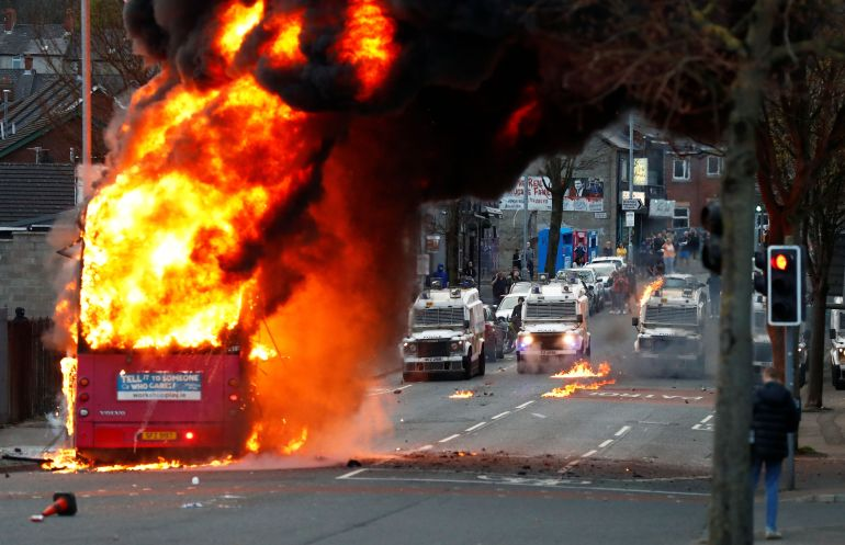 Police vehicles in front of a burning bus in Belfast, Northern Ireland, on April 7