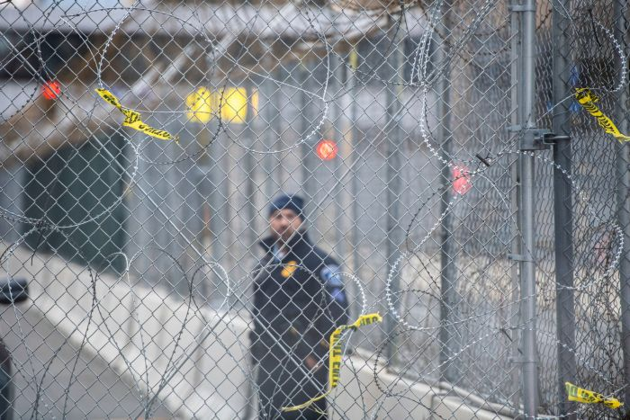 A police officer looks out at protestors through fencing and barbed wire near the Hennepin County Government Center on April