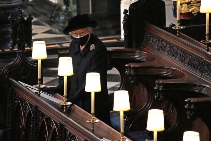 Queen Elizabeth II watches as pallbearers carry the coffin of Prince Philip.