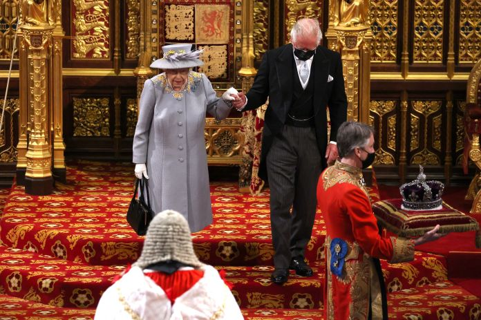 An image showing the queen's crown being carried into the chamber ahead of her on a cushion.