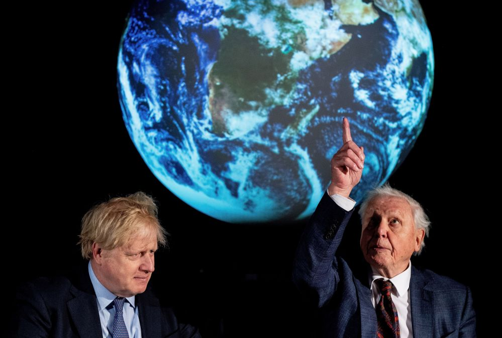 Britain's Prime Minister Boris Johnson sits with British broadcaster and conservationist David Attenborough, during an event