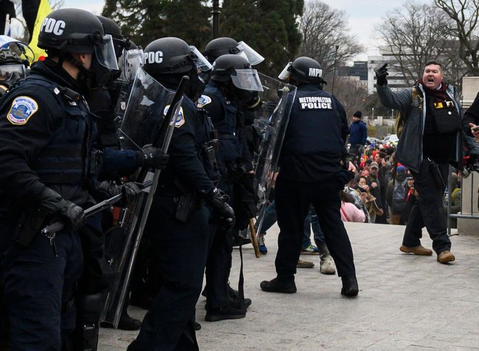 Russell Taylor, right, flips over to the cops at the Capitol.
