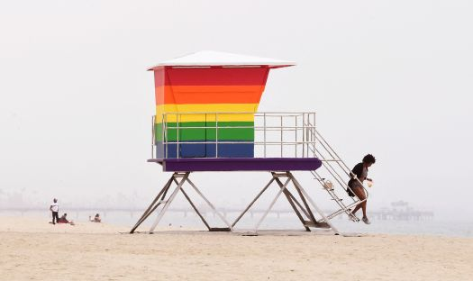 A woman steps off the stairs of a rainbow-colored lifeguard tower in Long Beach, California, on June 16. California has