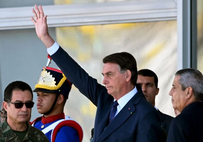 Flanked by a former general and the commander of the navy, far-right Brazil President Jair Bolsonaro watches a military parad