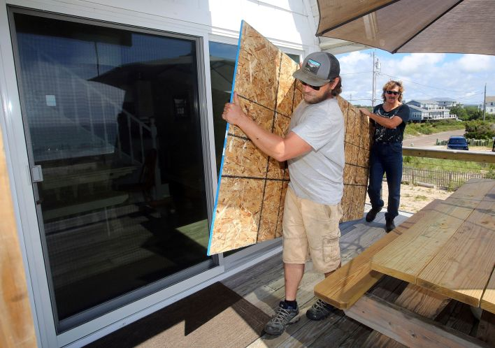 James Masog, center, and Gary Tavares, right, move particle board into place to board up the sliding glass doors of a client'