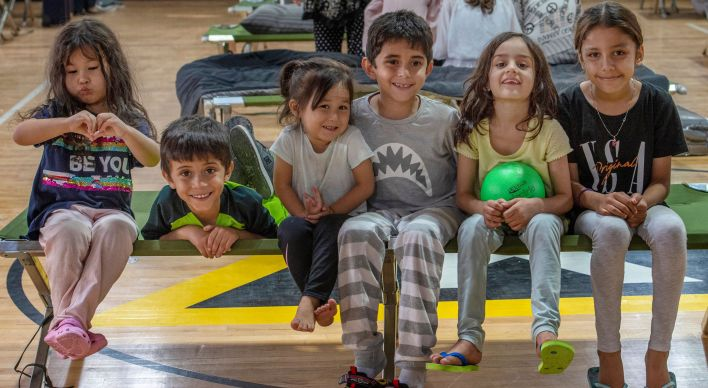 Children pose for a picture in a gym in an undisclosed location in the Middle East region on Aug. 20 after being evacuated on