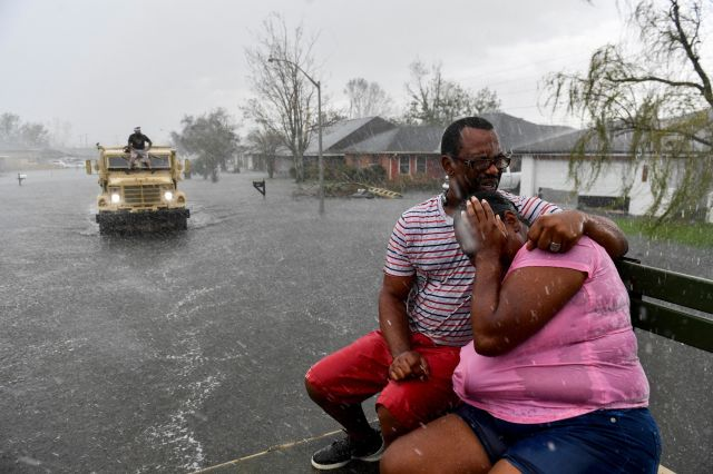 People react as a sudden rain shower soaks them with water while riding out of a flooded neighborhood in a volunteer high wat