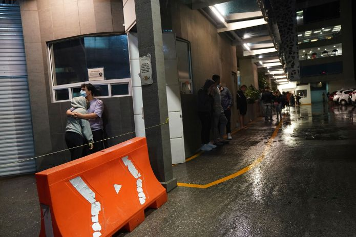 People gather outside a building after a strong earthquake was felt in Mexico City on Tuesday.