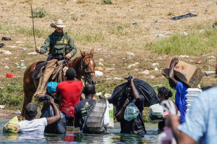 A US Border Patrol agent on horseback uses the reins as he tries to stop Haitians
