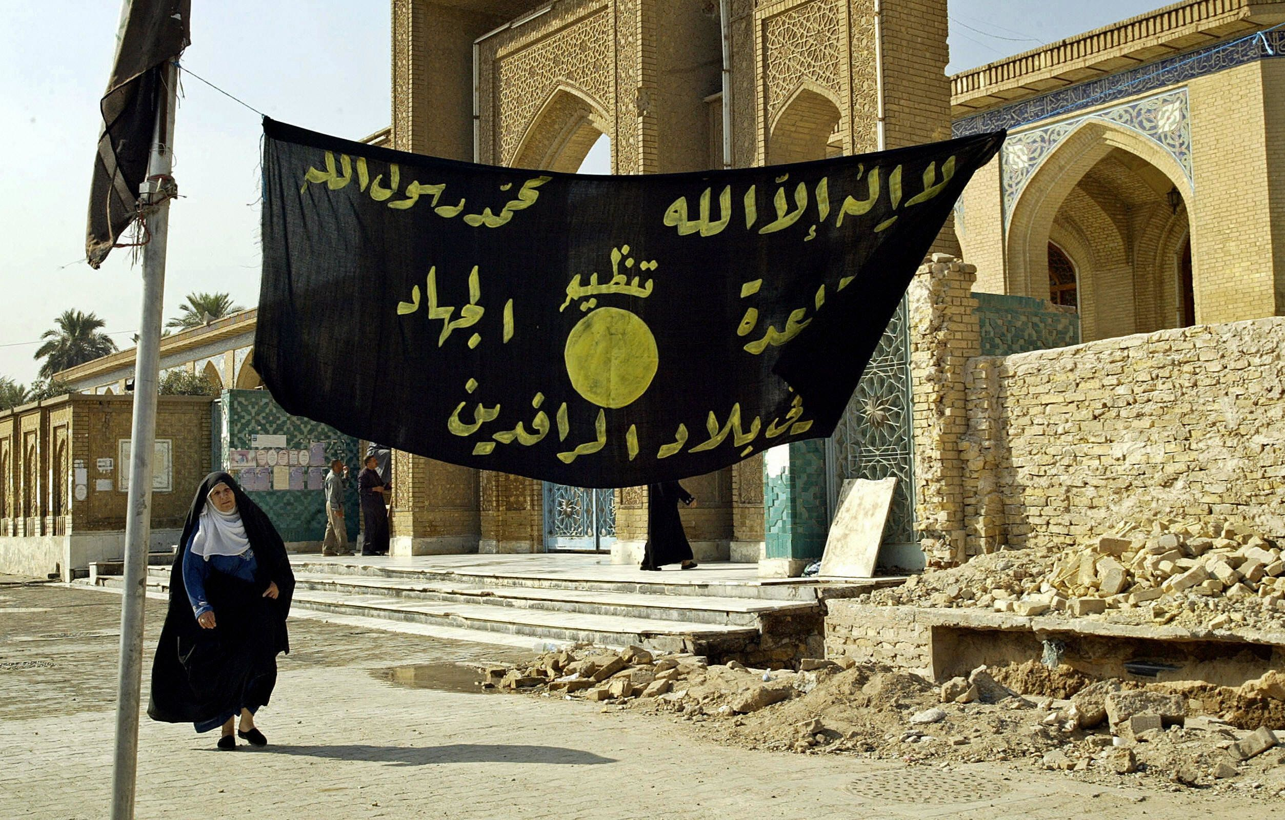 "<span class='image-component__caption' itemprop=""caption"">An Iraqi woman walks past a jihadi banner in Baghdad in 2004.</span>"