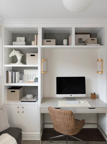 neutral home office with white built-ins and brass wall sconces