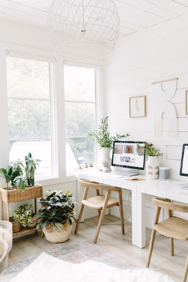 Boho office with natural sunlight, large windows, and white walls