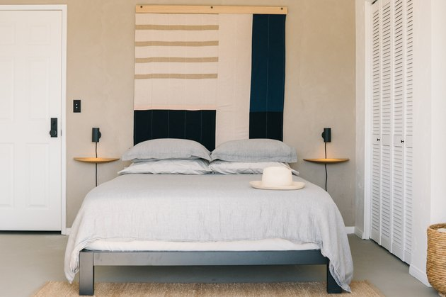 tan bedroom decorated with calming colors and bold geometric wall art piece.
