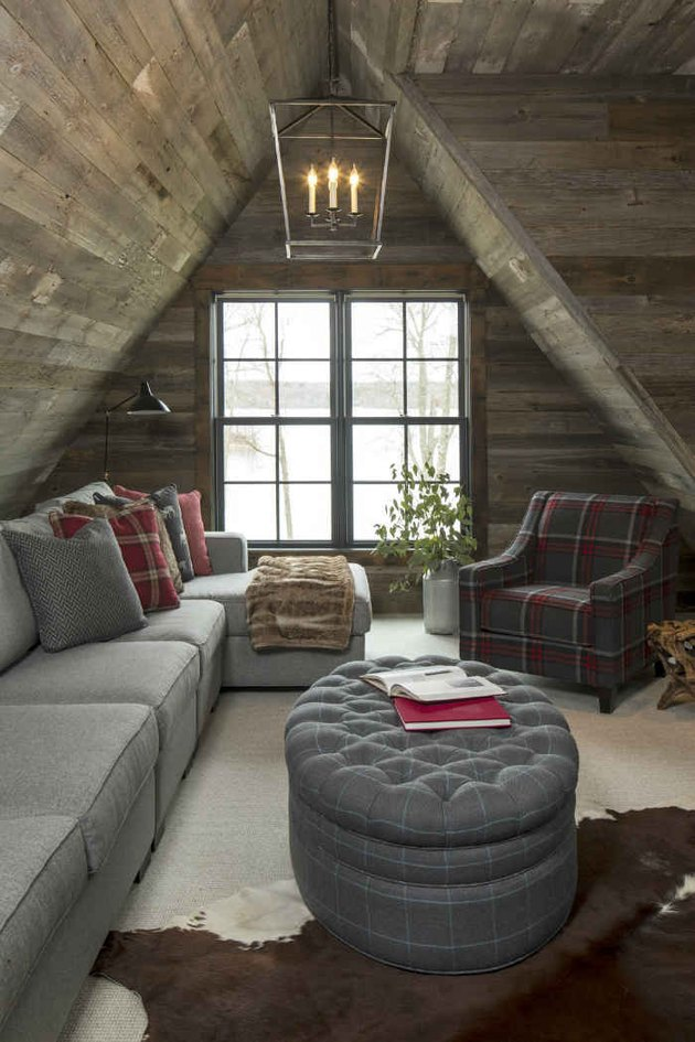 Small attic ideas for a space with high angled roof and wooden paneling along the ceiling.