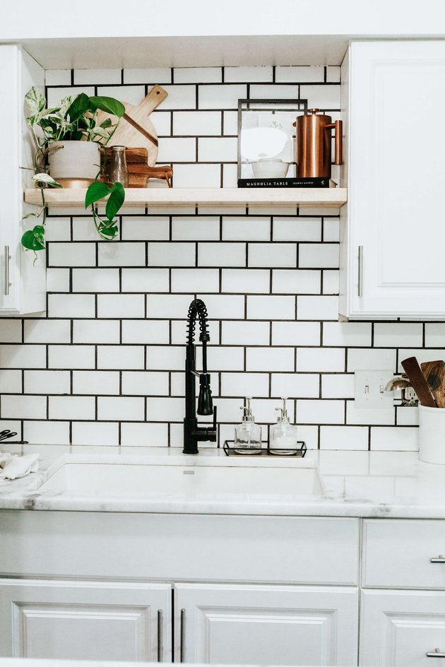 Industrial farmhouse kitchen with black faucet and black and white subway tile backsplash