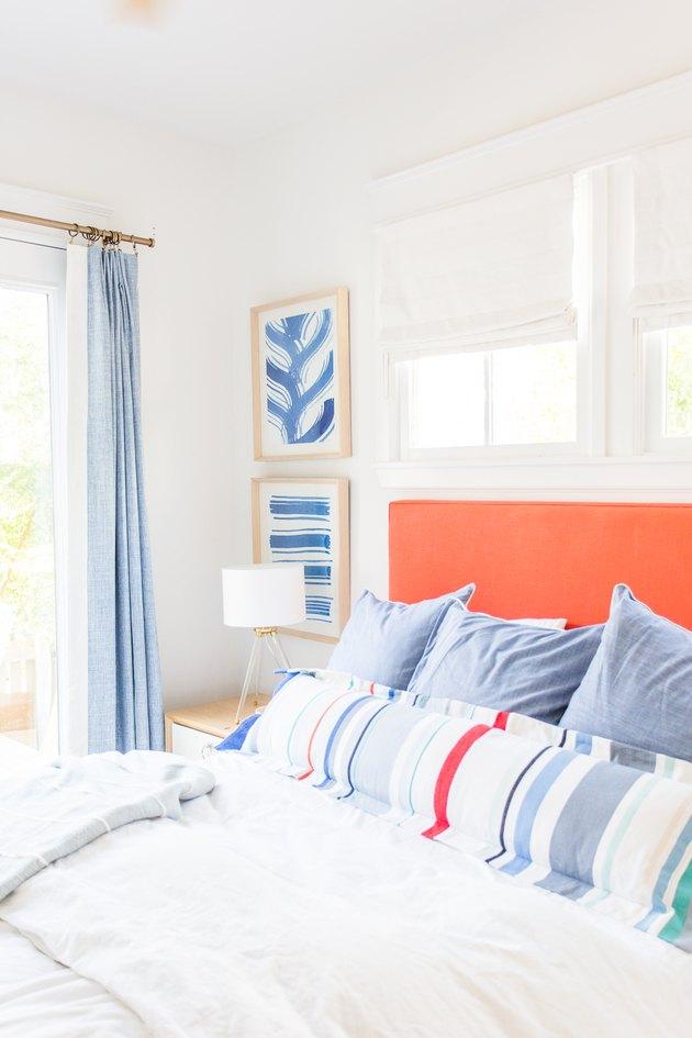 Classic coastal bedding idea with orange headboard and striped lumbar pillow