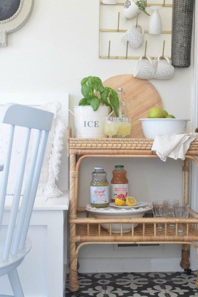 Farmhouse dining room storage idea with rattan cart