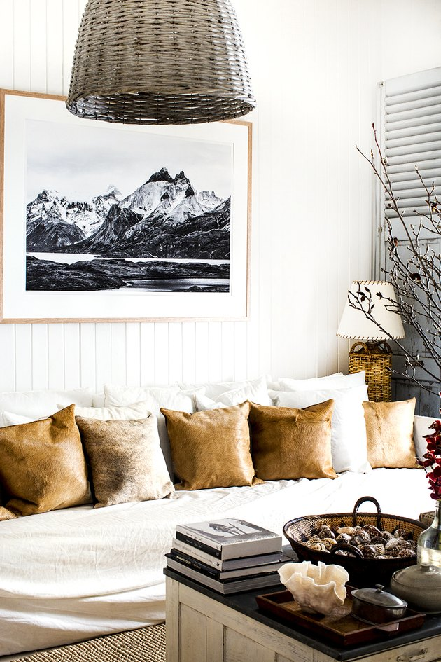living room with sofa filled with leather accent pillows and vertical shiplap walls