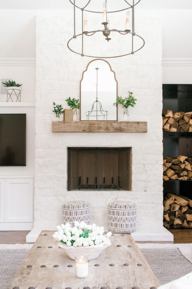 modern farmhouse fireplace with stacked wood and white brick wall surround