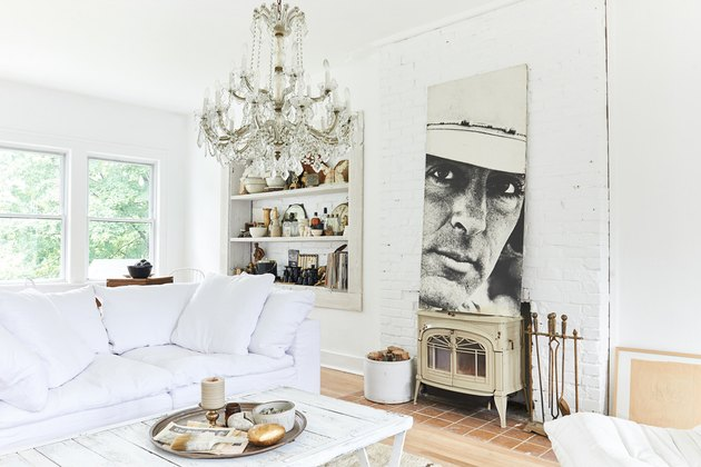 renovated white farmhouse with crystal chandelier and open shelving