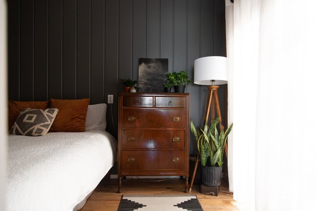 Bedroom with vintage decor and dark wall