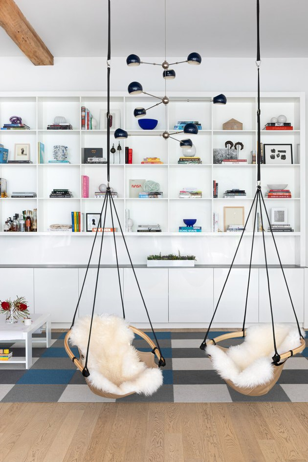 book storage in A modern bedroom with two ceiling-mounted swing chairs and bookshelves.