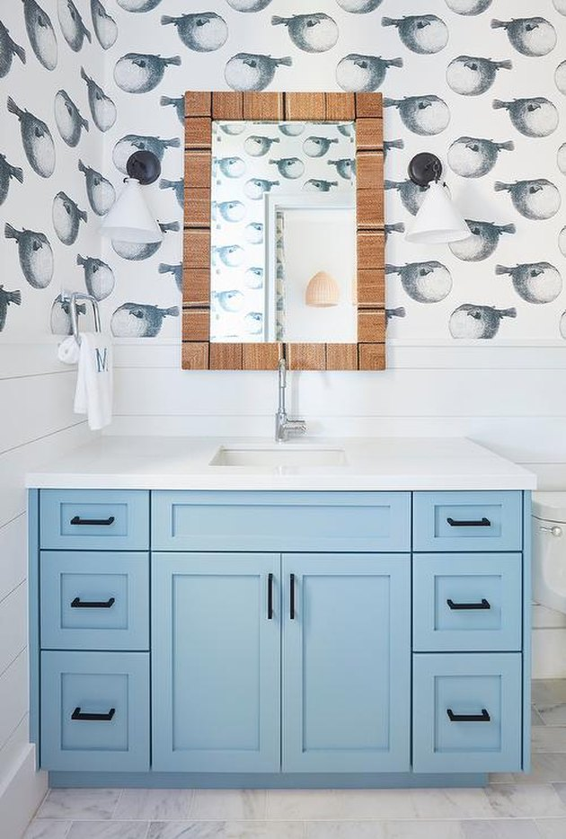 small bathroom wallpaper with blow fish print and blue vanity cabinet