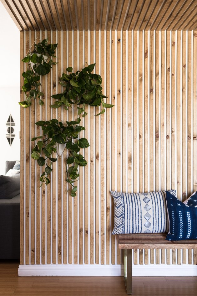 A wood panel wall, and hanging plants, and a wood bench with Shibori pillows.