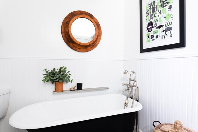 small bathroom wall art with black and white clawfoot tub with round mirror hanging above it