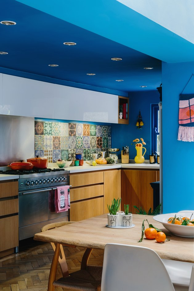 blue walls in maximalist kitchen with wood cabinets and patterned tile backsplash