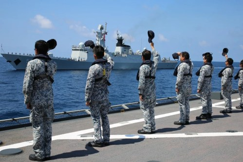 Singapore naval servicemen wave to a departing Chinese frigate after a previous joint exercise. Photo: Xinhua