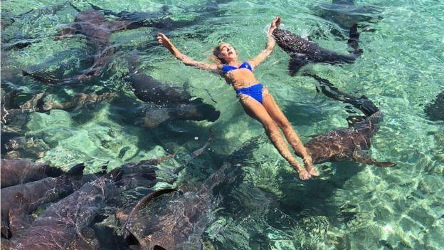 la Mujer nadando con tiburones