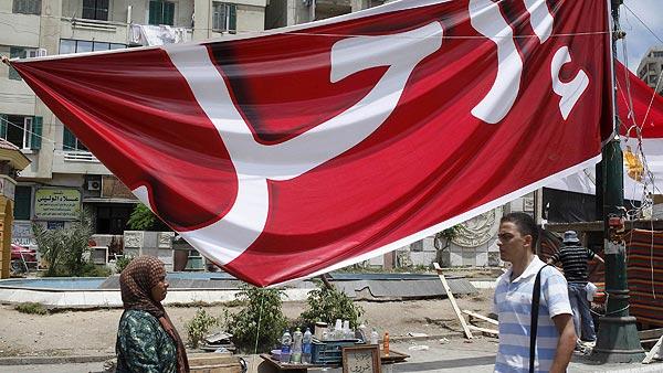 """Viandantes pasan frente a una pancarta con el lema """"Fuera"""", dirigido a Morsi, en Alejandría"""