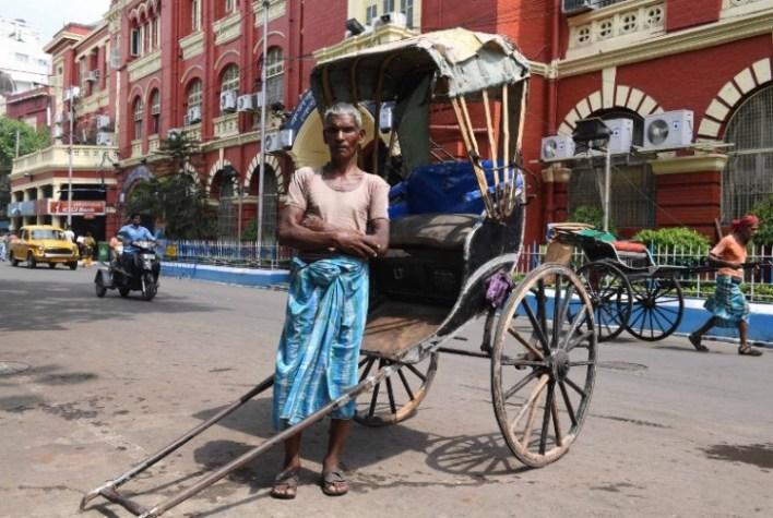 Mohammad Ashgar, 65, an Indian rickshaw puller, poses for a photograph next to his rickshaw in Kolkata on April 21, 2018.