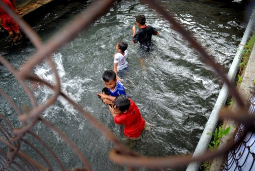 Children attempt to catch the offerings, including chicken and duck, in the water.