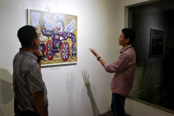 Jefri Chaniago (right) of Kiniko Art Management explains an artwork by Heri Dono to a visitor at the