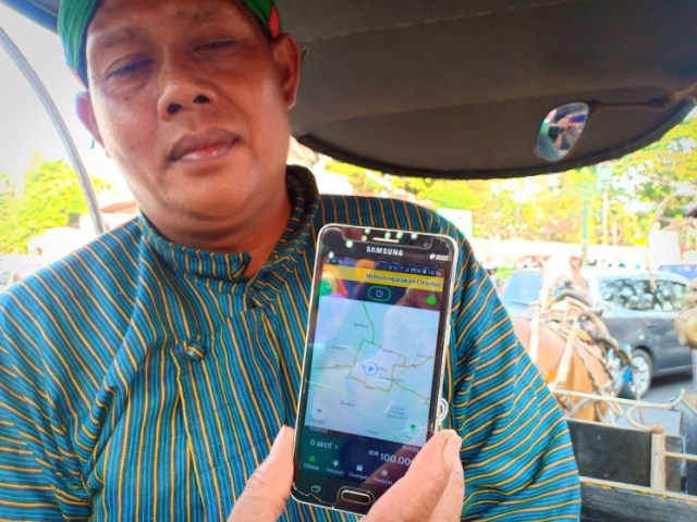 Riyanto, a horse-drawn carriage driver shows the GrabAndong app on his smartphone on Aug. 24.