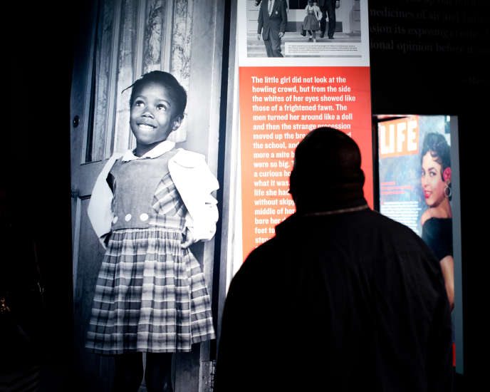 A man in front of a photograph, taken in 1960 in New Orleans, of Ruby Bridges Hall, the first child of color to have entered the door of a school for white children in the United States.