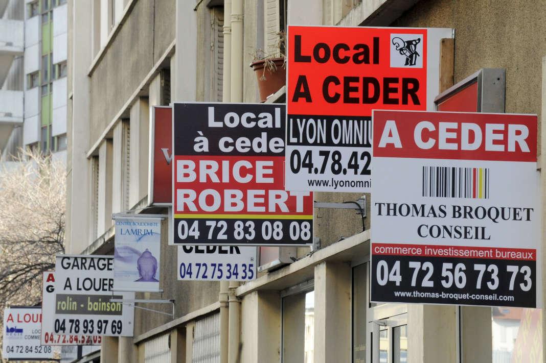 """Des pancartes """"local a ceder"""" dans une rue commerçante."""