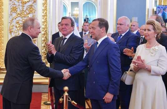 Le président russe Vladimir Poutine serrant la main deDmitry Medvedev, en présence de l'ancienchancelier allemand Gerhard Schröder, et la femme de M. Medvedev, à Moscou, le 7 mai.
