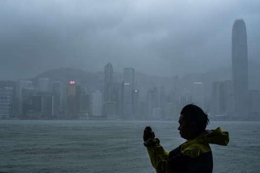 Un homme prend une photo à Hong Kong, en Chine, à l'approche du super Typhoon Mnagkhut, le 16 septembre.