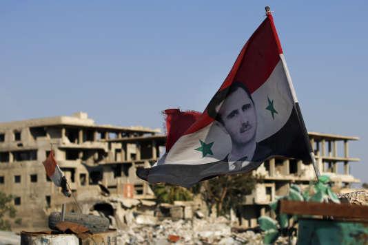 Le 15 juillet 2018, un drapeau syrien flotte au-dessus des ruines de Douma, dans la Ghouta orientale, près de Damas.