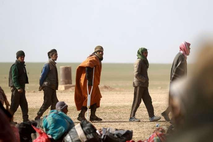 Contrôle de civils par les Forces démocratiques syriennes, le 26 janvier 2019, àBaghouz, près de la frontière irakienne.