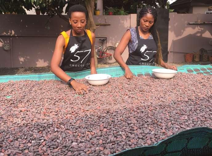 Kimerley et Priscilla Addison en train de trier des fèves biologiques d'un producteur de l'est du pays dans la cour de leur entreprise, à Accra, en février 2019.
