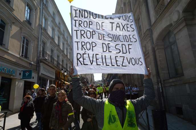 "On April 13, in Laval, protesters parade for the 22nd consecutive Saturday of gathering ""yellow vests""."