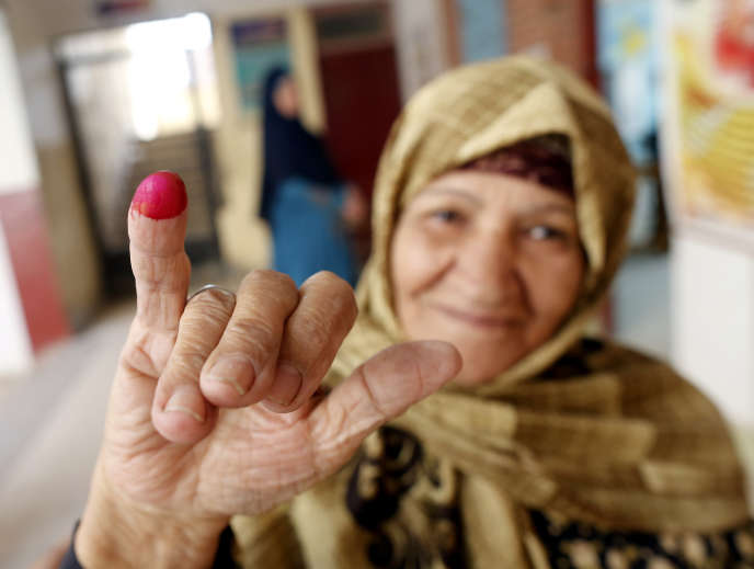An Egyptian woman shows her inked finger, a sign she voted on April 21 in Cairo.