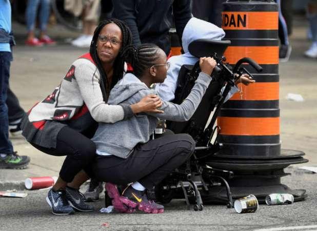 Des personnes se protègent après l'annonce de coups de feu près du Nathan Phillips Square à Toronto, lors de la parade des Raptors, le 17 juin.