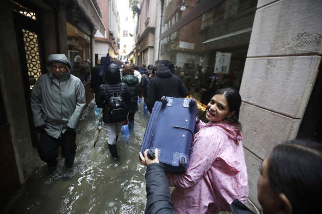 Tourists carry their luggage in the streets where the water level rose exceptionally on November 12.